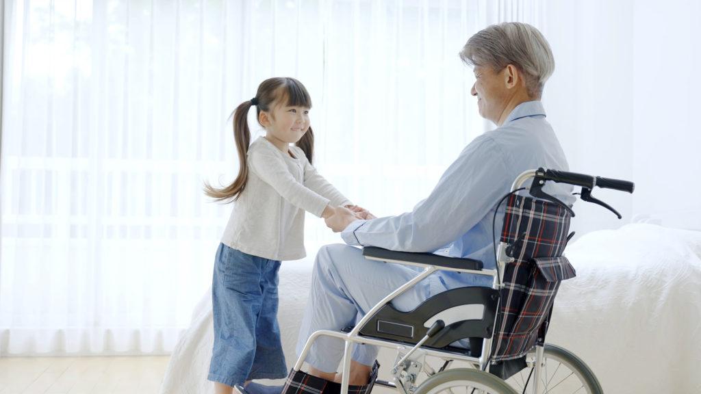 車椅子に乗るおじいちゃんと孫